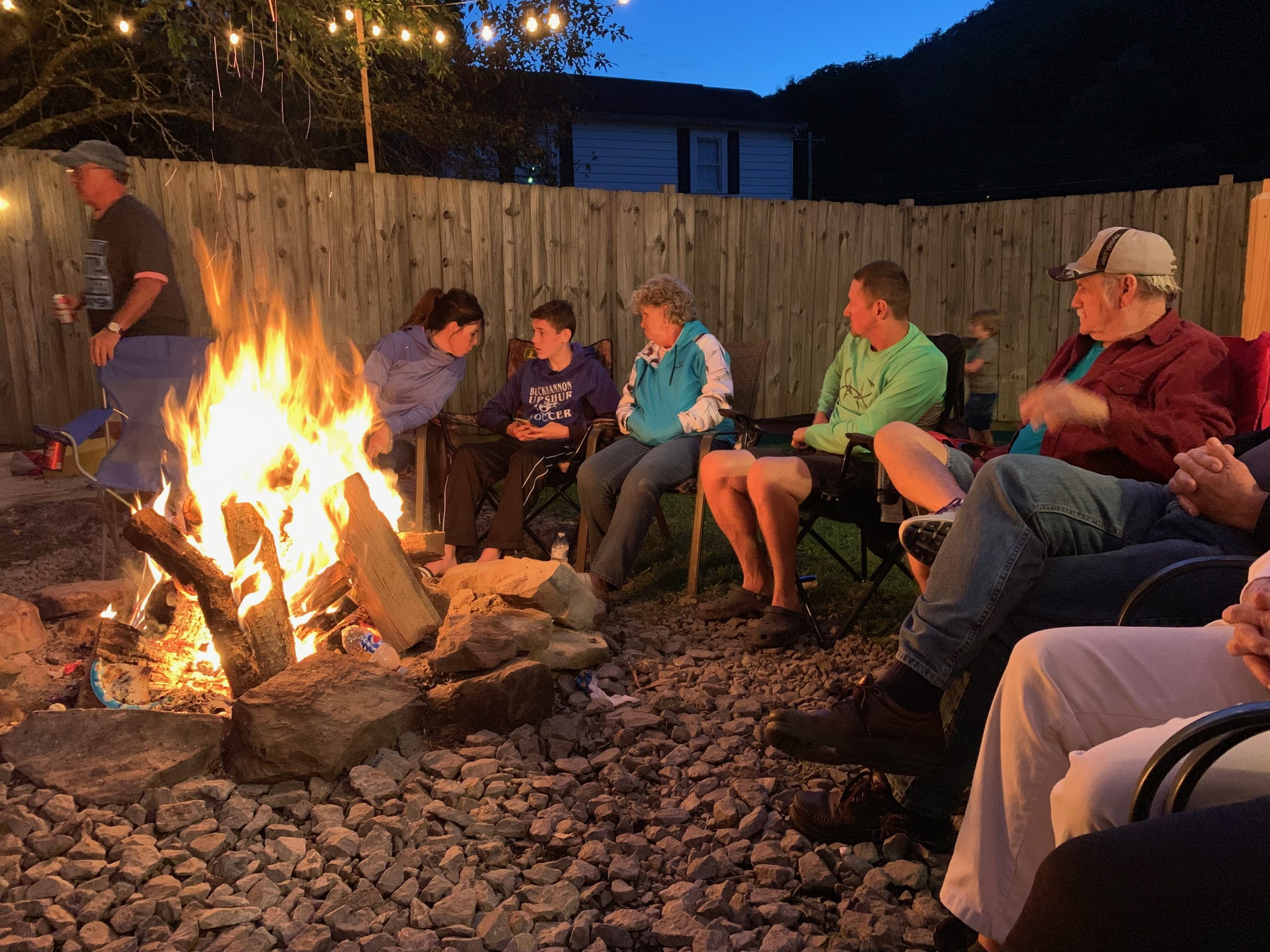 Family gathers around the campfire.